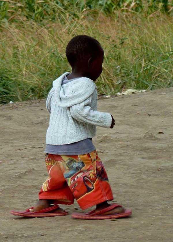 Kleiner Junge in großen Flipflops