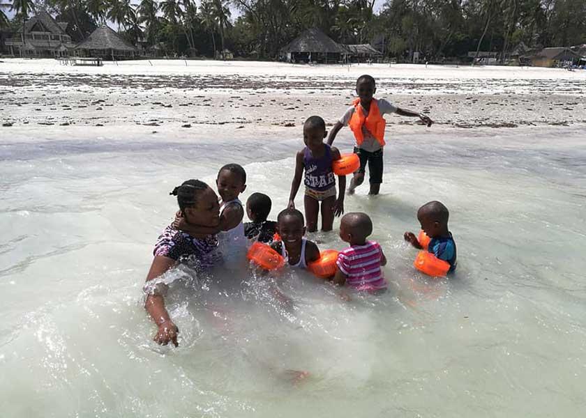 Betreuerin mit Kindern im Meer